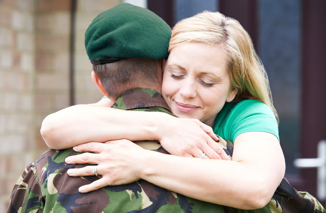 Wife lovingly embracing soldier husband